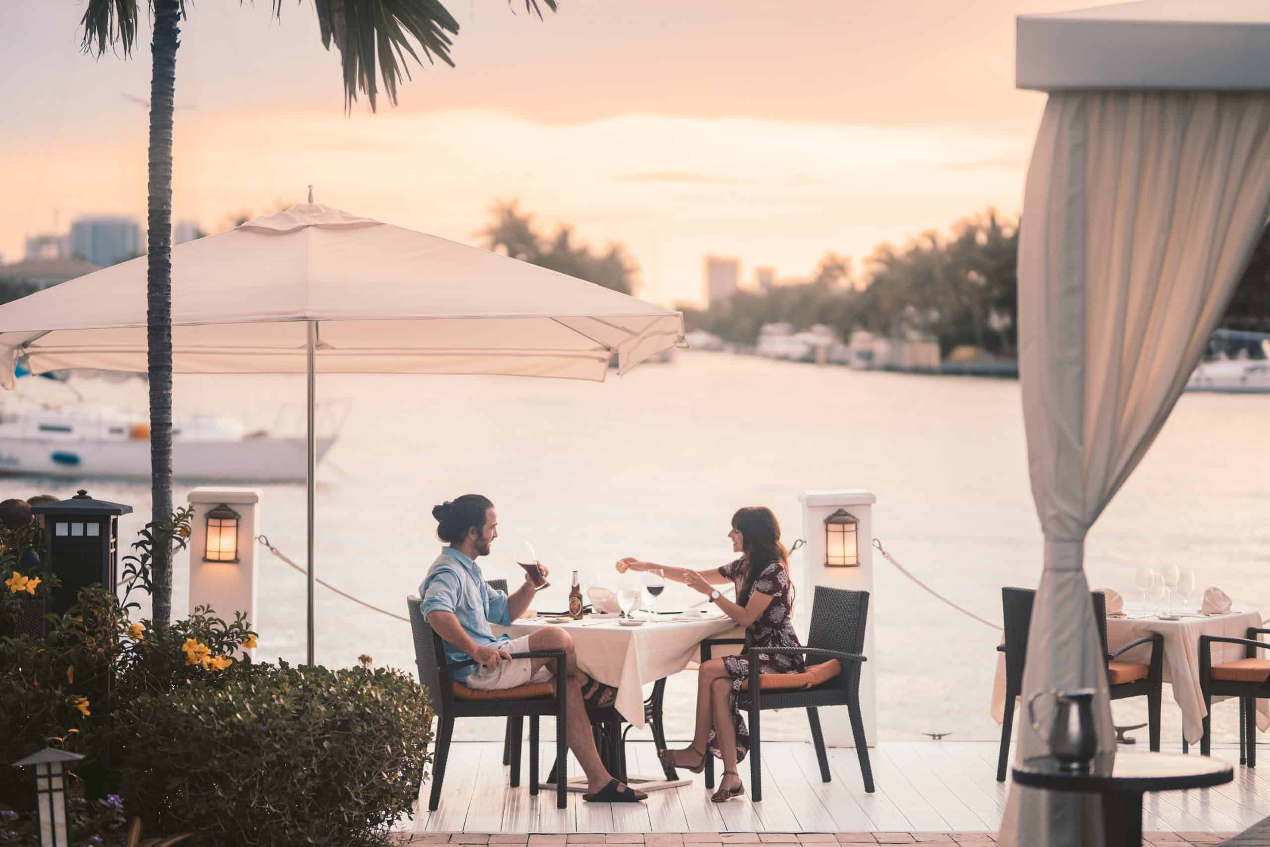 couple sitting at a waterfront restaurant table at sunset