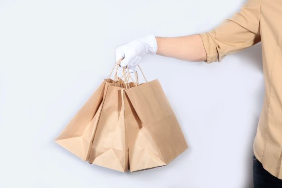 delivery person delivering food in paper bags