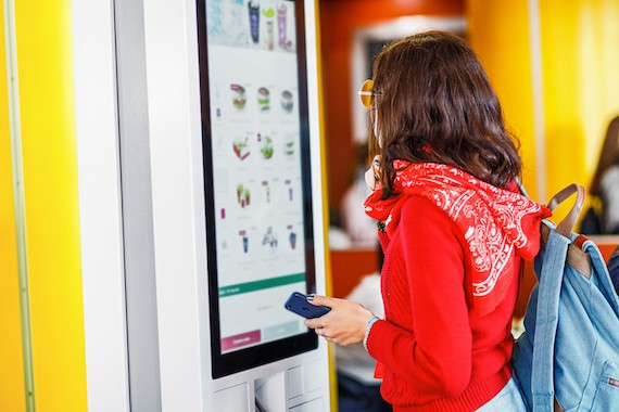 woman ordering at digital kiosk in restaurant