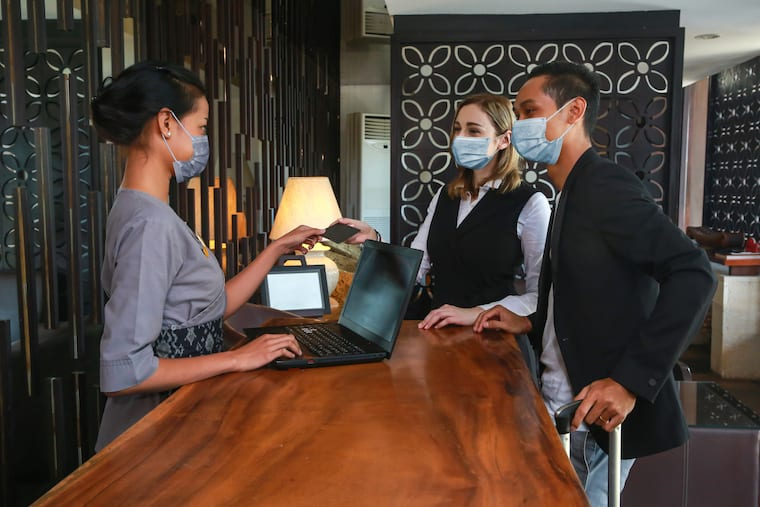 two people checking into hotel with facemasks