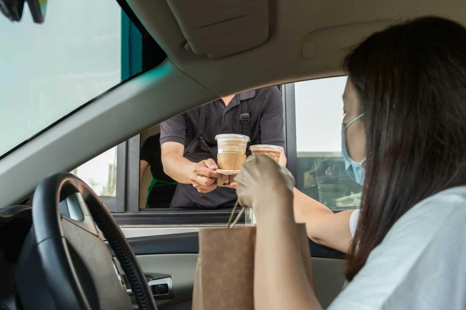 woman getting food through drive thru window