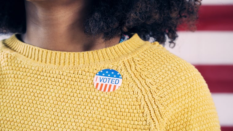 shot of woman's yellow sweater with I Voted sticker