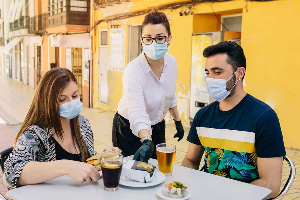 couple dining outside during cover wearing masks